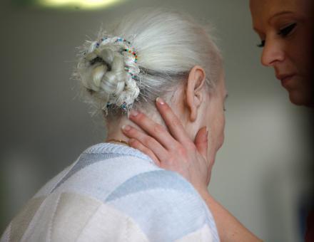 Betreuerin hält eine Frau im Altersheim behutsam am Hals