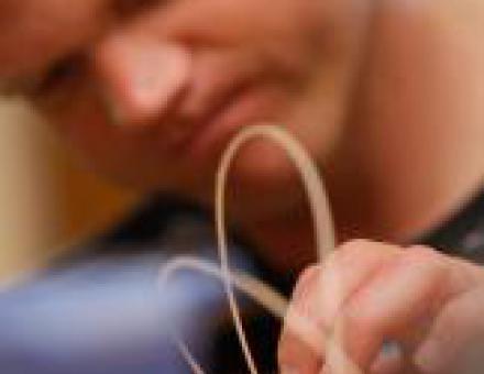 Ein Klient bindet konzentriert eine Masche