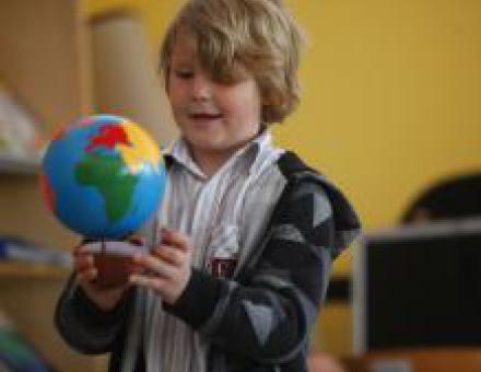 Ein Kind in der Schule untersucht aufgeregt einen Globus