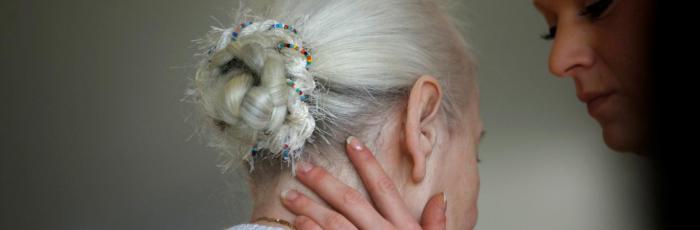 Header Bild: Betreuerin hält eine Frau im Altersheim behutsam am Hals