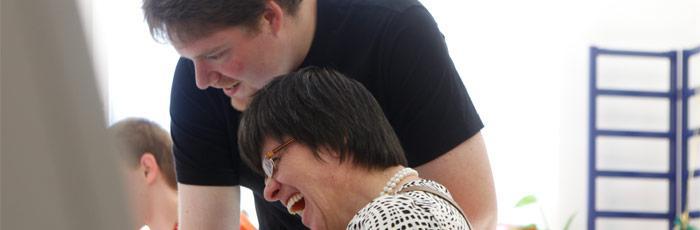 Header Bild: Betreuer hält Frau am Arm