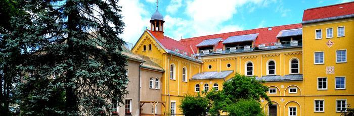 Header Bild: Die Hinterseite vom großen Haus Harbach an einem schönen Sommertag
