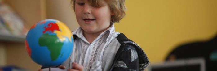 Header Bild: Ein Kind in der Schule untersucht aufgeregt einen Globus